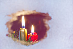 Christmas candles on a snowy window Royalty Free Stock Photos