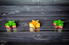 Christmas candles stars. In front of a wooden background Stock Photos