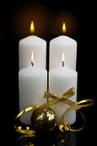 Christmas candles table setting. With gold baubles bow and ribbon over black background Stock Image