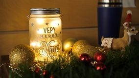 Christmas candles with Christmas tree decorations and a white candlestick house, white and blue and tree branches with a. Christmas garland on a wooden table Royalty Free Stock Images