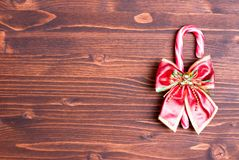 Christmas candy cane with bow on the board brown Stock Photography