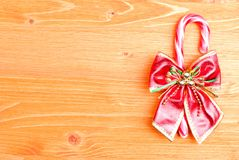 Christmas candy cane with bow on the board yellow Royalty Free Stock Photography