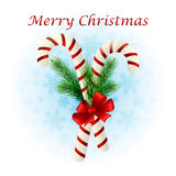 Christmas candy cane decorated with a bow and tree branches. Christmas candy cane decorated with a bow and Christmas tree branches Stock Photos