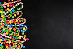 Christmas candy cane with candy drops over black background with. Copy space, flat lay stock photography