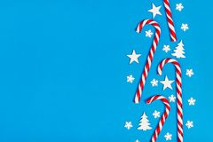 Christmas candy cane lied evenly in row on blue background with decorative snowflake and star. Flat lay and top view.  Stock Image