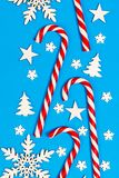 Christmas candy cane lied evenly in row on blue background with decorative snowflake and star. Flat lay and top view.  Stock Photos
