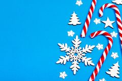 Christmas candy cane lied evenly in row on blue background with decorative snowflake and star. Flat lay and top view.  Royalty Free Stock Photo