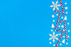 Christmas candy cane lied evenly in row on blue background with decorative snowflake and star. Flat lay and top view.  Royalty Free Stock Image