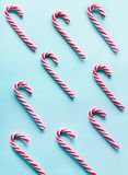 Christmas candy cane lied evenly in row on blue background. Flat lay and top view. Pattern. Christmas candy cane lied evenly in row on blue background. Flat lay Stock Images