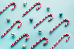 Christmas candy cane lied evenly in row on blue. Flat lay and top view. Christmas candy cane lied evenly in row on blue background. Flat lay and top view Royalty Free Stock Image