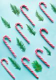 Christmas candy cane lied evenly in row on blue. Flat lay and top view. Christmas candy cane lied evenly in row on blue background. Flat lay and top view Royalty Free Stock Photos