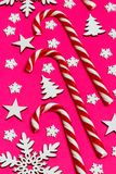 Christmas candy cane lied evenly in row on pink background with decorative snowflake and star. Flat lay and top view.  Royalty Free Stock Photos