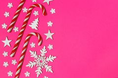 Christmas candy cane lied evenly in row on pink background with decorative snowflake and star. Flat lay and top view.  Royalty Free Stock Image