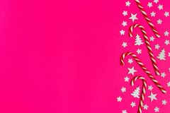 Christmas candy cane lied evenly in row on pink background with decorative snowflake and star. Flat lay and top view.  Stock Image