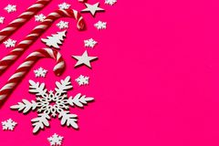 Christmas candy cane lied evenly in row on pink background with decorative snowflake and star. Flat lay and top view.  Royalty Free Stock Images