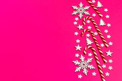 Christmas candy cane lied evenly in row on pink background with decorative snowflake and star. Flat lay and top view.  Stock Photography