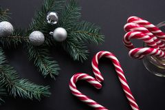 Christmas candy cane with silver evening balls and green fir tree on black background. Christmas concept. Top view and copy space, Royalty Free Stock Images