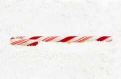 Christmas candy cane on a snow. Background Royalty Free Stock Photo