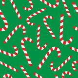 Christmas candy cane vector seamless pattern. Festive green background with sweet red and white candy canes Royalty Free Stock Image