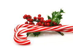 Christmas candy canes. With a branch of holly on a white background Royalty Free Stock Images