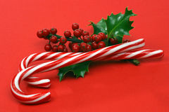 Christmas candy canes. With a branch of holly on a red background Stock Photos