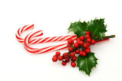 Christmas candy canes. With a branch of holly on a white background Stock Images