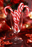 Christmas candy canes. Sweet candy canes for Christmas in glass in red tone Royalty Free Stock Photography