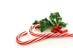Christmas candy canes. With a branch of holly on a white background Stock Photos