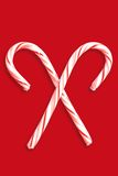 Christmas Candy Canes. Two candy canes on a dark red background Royalty Free Stock Images