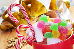 Christmas candy canes. A bowl with different candies, such as candy canes, on a table with some christmas ornaments, such as a golden an silver garland and a Royalty Free Stock Photo