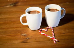Christmas candy canes and cups on wooden table Stock Photos