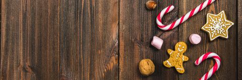 Christmas Candy Canes, Gingerbreads Of Different Shapes, Hazelnuts, Walnuts On A Brown Wooden Table. Copy Space. Stock Photo
