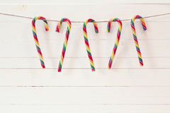 Christmas Candy Canes hang on the white wooden background. Stock Images