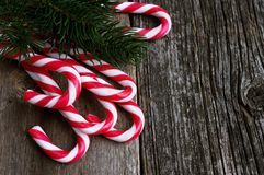 Christmas candy canes on old wooden table with fir branch. Red candy canes on old wooden table with fir branch.Copy space Stock Photos
