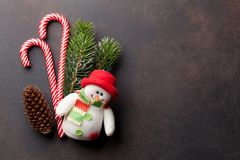 Christmas candy canes, snowman toy and fir tree. Christmas candy canes, snowman toy and snow fir tree on stone table. Top view with space for your greetings Stock Image