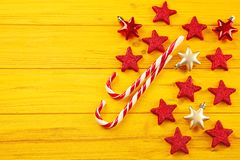 Christmas candy canes and stars on yellow background. Christmas candy canes and stars on yellow wooden background Royalty Free Stock Photography