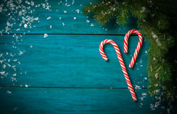 Christmas Candy Canes. Christmas tree branch with candy cane on wooden table. Top view with copy space Stock Image