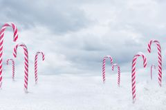 Christmas candy. Peppermint cane with snowfall on blue clouds background Stock Photos