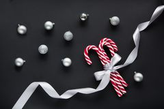 Christmas candy with silver ribbon and ball on black background. Christmas background. Top view and copy space. Royalty Free Stock Photos
