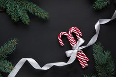 Christmas candy with silver ribbon and green fir tree on black background. Christmas background. Top view. Stock Images