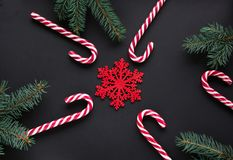 Christmas candy with silver ribbon, green fir tree, snowflake on black background. Christmas background. Top view and copy space Stock Image