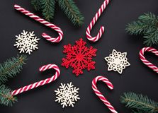 Christmas candy with silver ribbon, green fir tree, snowflake on black background. Christmas background. Top view. Royalty Free Stock Photo