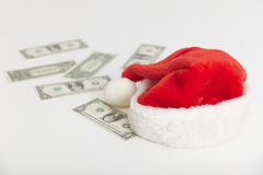 Christmas cap and dollars on white background Stock Images