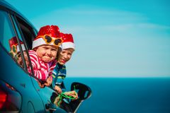 Christmas car travel- happy kids travel in winter at sea. Beach stock image
