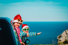 Christmas car travel- happy kids travel in winter at sea. Beach stock images