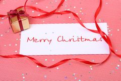 Christmas card. Card with a congratulation. The gift is tied up by a red tape Royalty Free Stock Photos