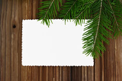 Christmas card. Empty paper form with fir-tree branches on old wooden background Stock Photos