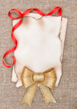 Christmas card with aged paper, bow and ribbon on burlap Royalty Free Stock Images