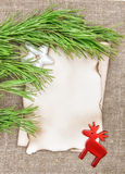 Christmas card with aged paper, fir branch and deer on burlap Stock Photography