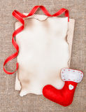 Christmas card with aged paper, sock and ribbon on burlap Royalty Free Stock Images